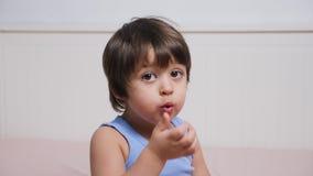 El niño pequeño cubre su boca con su mano metrajes