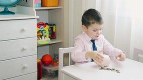 El niño pequeño cuenta el dinero acumulado en la hucha 1080 HD almacen de metraje de vídeo