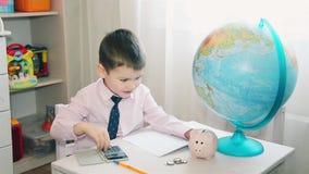 El niño pequeño cuenta sus ahorros en una calculadora HD almacen de video