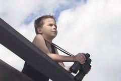 El niño pequeño dañoso sostiene los prismáticos en sus manos y pares en la distancia Fotos de archivo libres de regalías