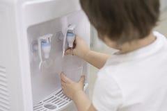 El niño pequeño da conseguir el agua de un refrigerador en una escuela o una guardería imagen de archivo