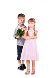 El niño pequeño da rosas a la muchacha aislada en blanco Foto de archivo