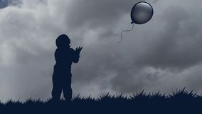 El niño pequeño deja el globo ir al cielo silueta inmóvil de un muchacho con un globo contra la perspectiva de metrajes
