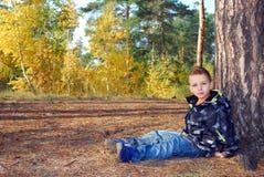 El niño pequeño del bosque se sienta cerca de un pino Fotografía de archivo