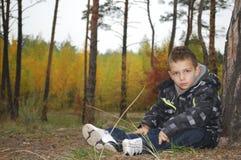 El niño pequeño del bosque se sienta cerca de un pino. Imagenes de archivo