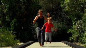 El niño pequeño divertido con la mamá corre y salta en la pista del trampolín en el parque metrajes