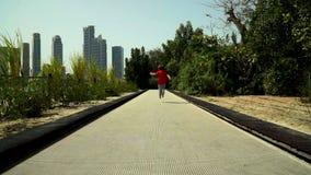 El niño pequeño divertido corre y salta en la pista del trampolín en el parque almacen de metraje de vídeo