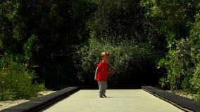 El niño pequeño divertido corre y salta en la pista del trampolín en el parque almacen de video