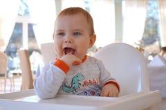 El niño pequeño divertido lindo salpica y hace muecas fotos de archivo libres de regalías