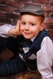 El niño pequeño elegante en un casquillo y las lanas conceden Imagenes de archivo