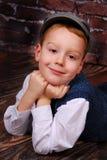El niño pequeño elegante en un casquillo y las lanas conceden Foto de archivo