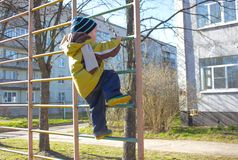 El niño pequeño, en guardería, en el patio, sube en el interruptor Imágenes de archivo libres de regalías