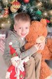 El niño pequeño en la sudadera con capucha que sostiene el oso de peluche en manos en el fondo de las decoraciones de la Navidad  Fotografía de archivo