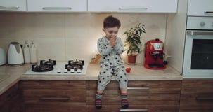 El niño pequeño en los pijamas se sienta en la tabla de cocina y feliz están aplaudiendo las manos y están dando besos con la man almacen de metraje de vídeo