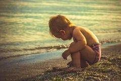 El niño pequeño en pantalones cortos rojos jugó en la playa Fotos de archivo