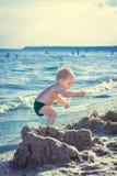 El niño pequeño en pantalones cortos verdes jugó en la playa Imagen de archivo libre de regalías