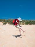 El niño pequeño en pantalones cortos y un sombrero con una mochila que cae en la arena en el azul del fondo Imagen de archivo