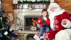El niño pequeño en revestimiento del ` s de Papá Noel, tenencia de Nicolás del niño y del santo chispea, Año Nuevo y celebración  almacen de video