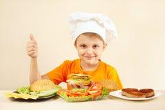 El niño pequeño en sombrero de los cocineros muestra cómo cocinar la hamburguesa Foto de archivo