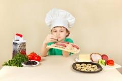 El niño pequeño en sombrero de los cocineros pone aceitunas en la corteza de la pizza Foto de archivo