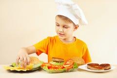 El niño pequeño en sombrero de los cocineros pone el queso en la hamburguesa Imagen de archivo