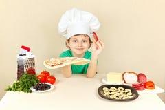 El niño pequeño en sombrero de los cocineros pone la salchicha en la corteza de la pizza Foto de archivo libre de regalías