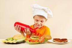 El niño pequeño en sombrero de los cocineros pone la salsa de tomate en la hamburguesa Imagen de archivo