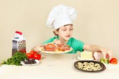 El niño pequeño en sombrero de los cocineros pone los ingredientes en la corteza de la pizza Imagenes de archivo