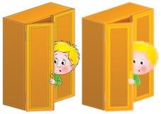El niño pequeño en susto está ocultando en el aparador Imagenes de archivo