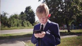 El niño pequeño en traje sostiene un smartphone y juega al juego en la calle