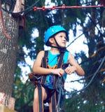 El niño pequeño en un casco protector y en el equipo especial pasa una carrera de obstáculos en la altura foto de archivo libre de regalías
