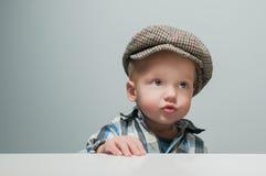 El niño pequeño en un casquillo se sienta en la tabla Fotografía de archivo
