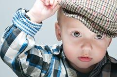 El niño pequeño en un casquillo se sienta en la tabla Fotos de archivo