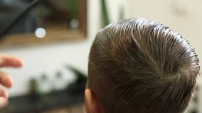 El niño pequeño en un corte de pelo en el peluquero se sienta en una silla almacen de metraje de vídeo
