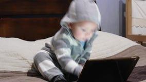 El niño pequeño en un traje rayado utiliza una tableta almacen de video
