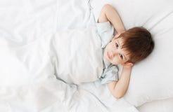 El niño pequeño en una cama Fotos de archivo libres de regalías