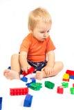 El niño pequeño en una camisa anaranjada es Lego jugado Foto de archivo