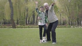 El ni?o peque?o en una camisa a cuadros y un viejo hombre positivo que agitan sus manos a la c?mara en el parque El nieto almacen de video