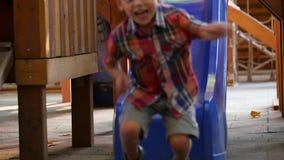 El niño pequeño en una camisa de tela escocesa rueda abajo la colina almacen de metraje de vídeo