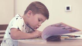 El niño pequeño encantador hace diligente tareas en libro de trabajo metrajes