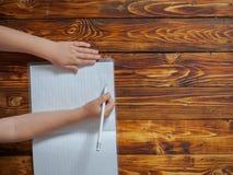 El niño pequeño escribe en el cuaderno que se sienta en el escritorio Fotografía de archivo libre de regalías