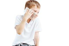 El niño pequeño escucha música y habla en el teléfono con el fondo blanco Foto de archivo libre de regalías