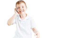 El niño pequeño escucha música y habla en el teléfono con el fondo blanco Fotos de archivo