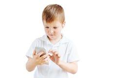 El niño pequeño escucha música y habla en el teléfono con el fondo blanco Fotografía de archivo