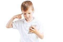 El niño pequeño escucha música y habla en el teléfono con el fondo blanco Imagenes de archivo