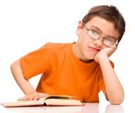 El niño pequeño está cansado leer su libro Imagen de archivo libre de regalías