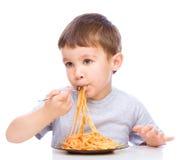 El niño pequeño está comiendo los espaguetis fotografía de archivo