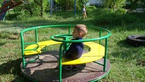 El niño pequeño está girando rápidamente en un carrusel en el parque Un juego del ` s del niño metrajes