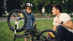 El niño pequeño está haciendo girar la rueda y pedales de bicicleta mientras que su padre está hablando con él en césped en parqu almacen de video