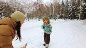 El niño pequeño está intentando al trineo y a la risa metrajes